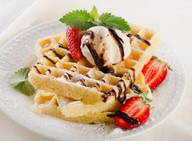 Belgiska våfflor serveras med glass, chokladsås och färska jordgubbar
